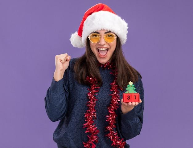 Vrolijke jonge blanke meisje in zonnebril met kerstmuts en slinger om nek houdt vuist en houdt kerstboom ornament geïsoleerd op paarse muur met kopie ruimte