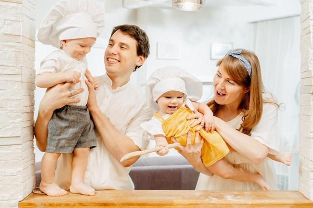 Vrolijke jonge blanke ouders houden de tweeling van een jongen en een meisje in de armen