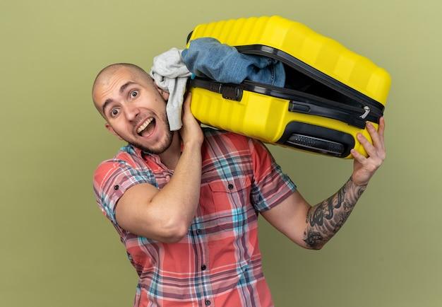 Vrolijke jonge blanke reiziger man met koffer op schouder geïsoleerd op olijfgroene achtergrond met kopie ruimte