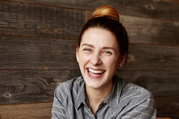 Vrolijke jonge blanke vrouw draagt haar rode haar in broodje hardop lachen
