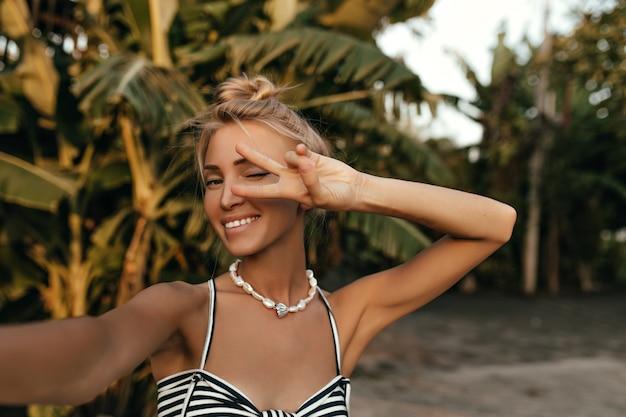 Vrolijke jonge blonde gelooide vrouw in gestreepte jurk en met parel ketting neemt selfie in tropisch park en toont vredesteken