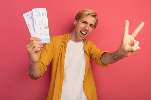 Vrolijke jonge blonde kerel die gele kaartjes van de t-shirtholding draagt die vredesgebaar tonen