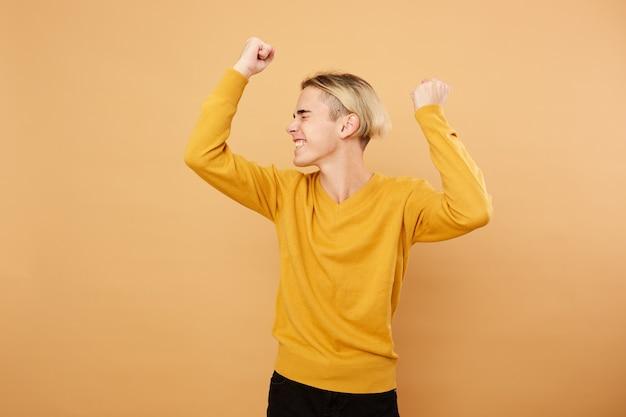 Vrolijke jonge blonde man gekleed in gele trui poseert in de studio op de beige achtergrond.