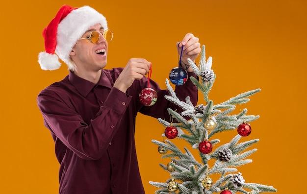 Vrolijke jonge blonde man met kerstmuts en bril staan in profiel te bekijken in de buurt van versierde kerstboom op oranje achtergrond