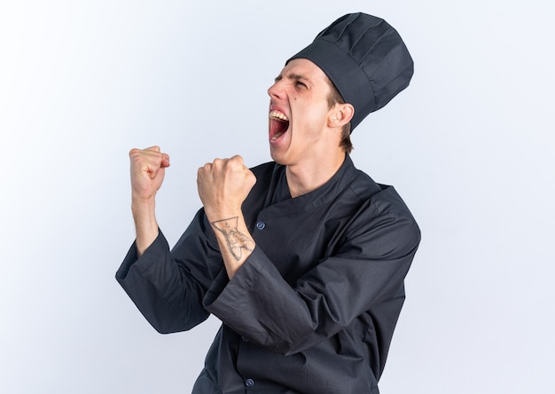 Vrolijke jonge blonde mannelijke kok in uniform van de chef en pet die in profielweergave staat en naar de zijkant kijkt en ja gebaar doet