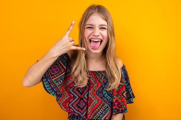 Vrolijke jonge blonde slavische meid die haar tong steekt en hoorns gebaart