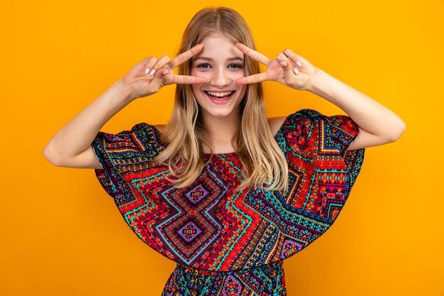 Vrolijke jonge blonde slavische meisje gebaren overwinning teken