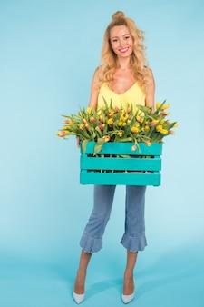 Vrolijke jonge blonde vrouw bloemist met doos tulpen op blauw.