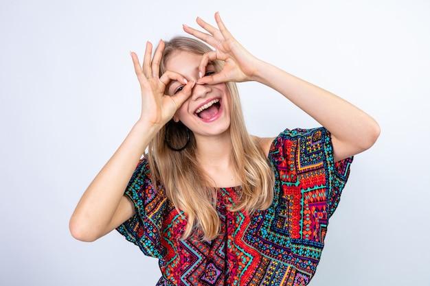 Vrolijke jonge blonde vrouw die door haar vingers kijkt