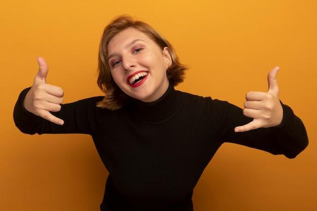 Vrolijke jonge blonde vrouw die naar de voorkant kijkt en een los gebaar doet dat op een oranje muur wordt geïsoleerd