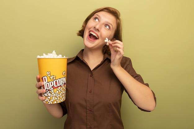 Vrolijke jonge blonde vrouw met emmer popcorn en popcorn stuk geïsoleerd op olijfgroene muur opzoeken