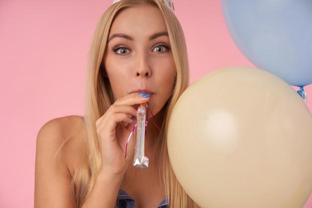 Vrolijke jonge blonde vrouw poseren in veelkleurige lucht ballonnen, partij hoorn in haar mond houden en camera gelukkig kijken, groeten van vrienden met speciale gelegenheid, geïsoleerd op roze achtergrond