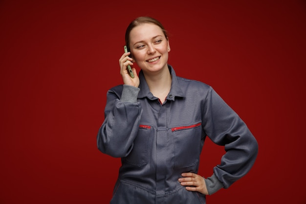 Vrolijke jonge blonde vrouwelijke ingenieur die uniform draagt ?? die op telefoon spreekt die hand op taille houdt die kant het glimlachen bekijkt