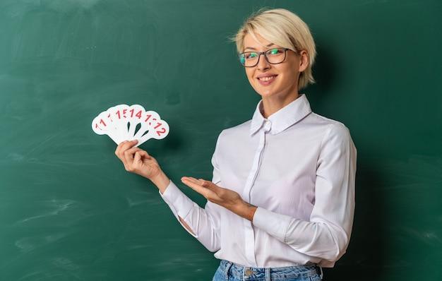 Vrolijke jonge blonde vrouwelijke leraar met een bril in de klas die voor het schoolbord staat en wijst naar nummerfans die naar de camera kijken