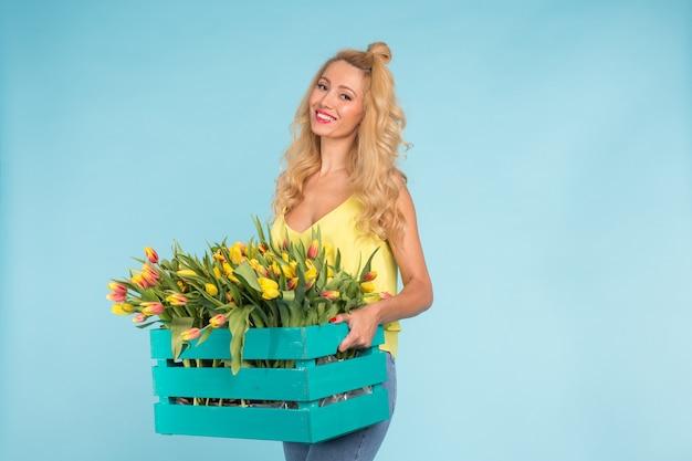 Vrolijke jonge blonde vrouwenbloemist met doos tulpen over blauwe muur met exemplaarruimte.