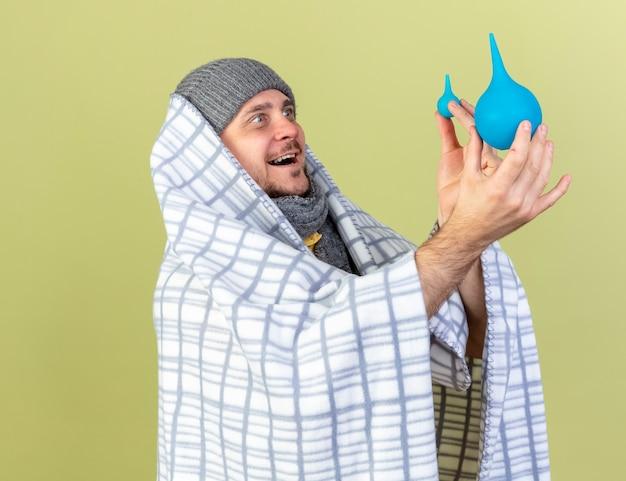 Vrolijke jonge blonde zieke man met muts en sjaal verpakt in geruite ruimen en kijkt naar klysma's geïsoleerd op olijfgroene muur