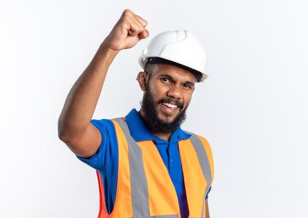 Vrolijke jonge bouwer man in uniform met veiligheidshelm staande met opgeheven vuist omhoog geïsoleerd op een witte muur met kopieerruimte