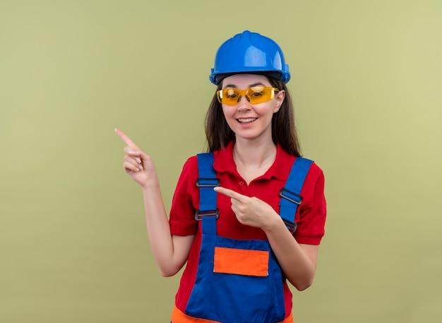 Vrolijke jonge bouwer meisje met blauwe veiligheidshelm en met veiligheidsbril wijst naar de kant met beide handen op geïsoleerde groene achtergrond met kopie ruimte