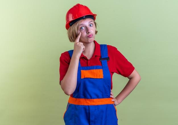 Vrolijke jonge bouwvrouw in uniform die ooglid naar beneden trekt met vinger geïsoleerd op olijfgroene muur