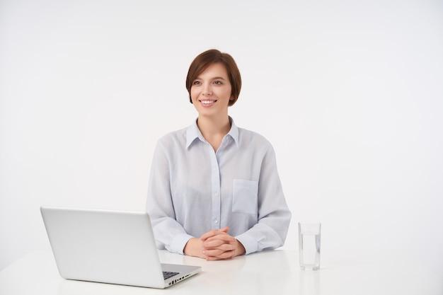 Vrolijke jonge bruinharige vrouw werknemer zittend op wit met moderne laptop en klaar om te ontmoeten, opzij kijken met een positieve glimlach