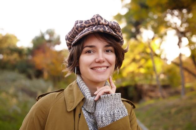 Vrolijke jonge bruinogige brunette vrouw met casual kapsel kijkt positief met charmante glimlach en raakt haar wang aan met opgeheven wijsvinger terwijl ze buiten poseren