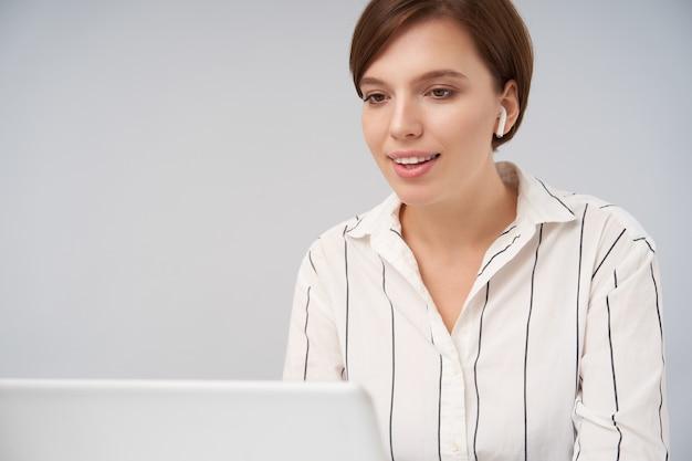 Vrolijke jonge bruinogige mooie brunette zakenvrouw met natuurlijke make-up oortelefoon dragen terwijl poseren op roze, in een goede bui zijn en aangenaam glimlachen