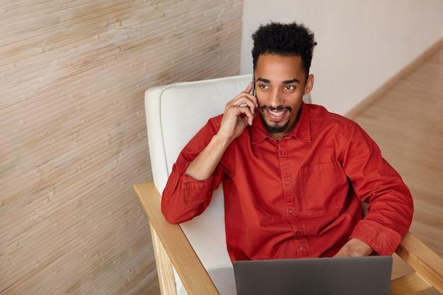 Vrolijke jonge brunette bebaarde donkere huid man glimlachend gelukkig terwijl het hebben van mooie telefoongesprek, zittend in een stoel met laptop op beige interieur