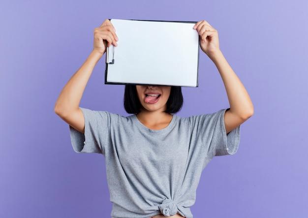 Vrolijke jonge brunette blanke vrouw sluit ogen met klembord en steekt tong geïsoleerd op paarse achtergrond met kopie ruimte