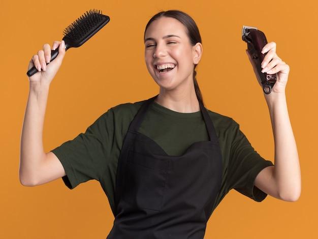 Vrolijke jonge brunette kapper meisje in uniform houdt haartrimmer en kam op oranje