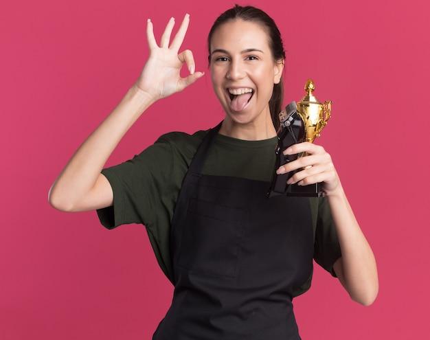 Vrolijke jonge brunette kapper meisje in uniform stucks tong gebaren ok handteken met tondeuse en winnaar beker op roze