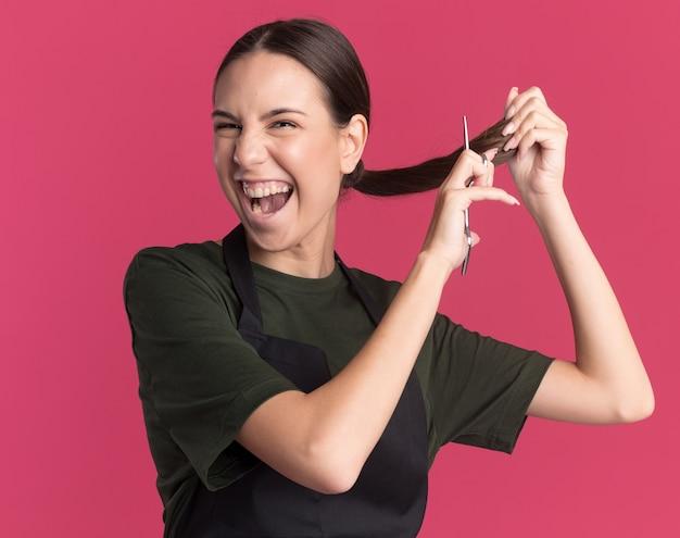 Vrolijke jonge brunette kappersmeisje in uniform doet alsof ze haar knipt met een haaruitdunnende schaar