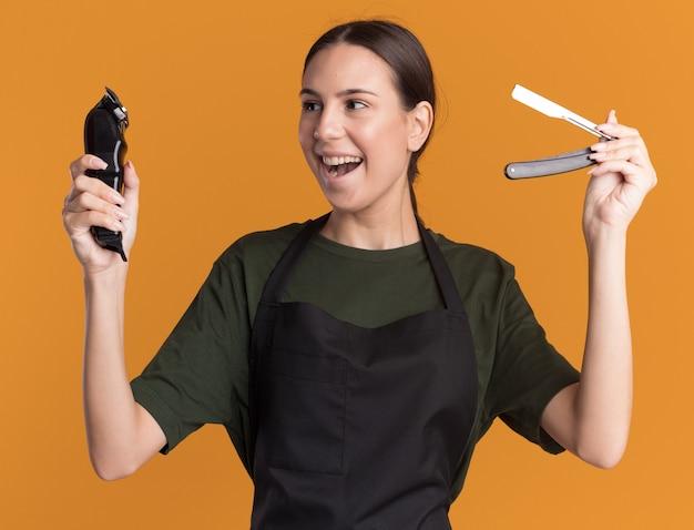 Vrolijke jonge brunette kappersmeisje in uniform houdt tondeuses en scheermes geïsoleerd op een oranje muur met kopieerruimte