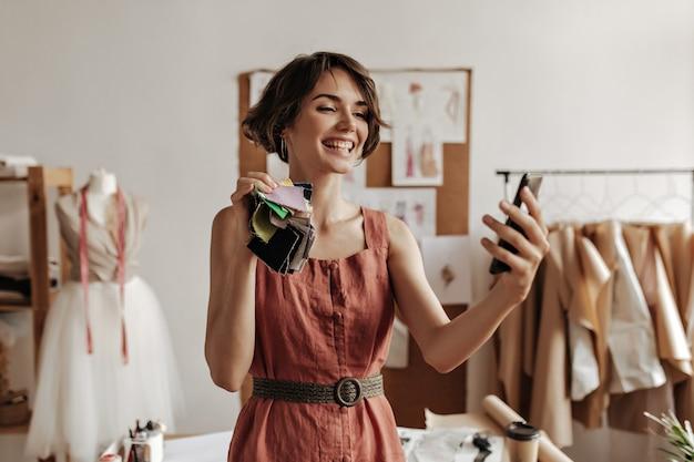 Vrolijke jonge brunette kortharige vrouw in linnen rode jurk glimlacht oprecht, houdt stukken textiel vast en neemt selfie op kantoor