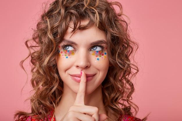 Vrolijke jonge brunette krullende dame met veelkleurige stippen op haar gezicht opzij kijken met een charmante glimlach en wijsvinger op haar lippen houden, geïsoleerd