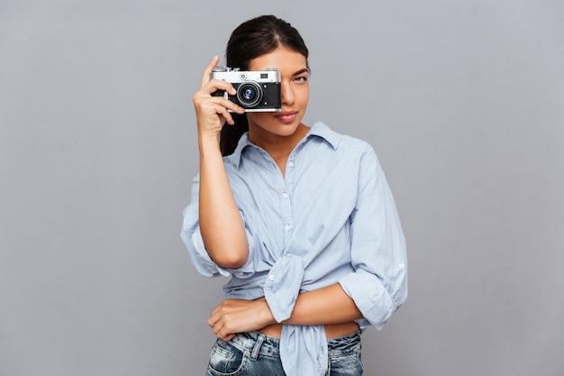 Vrolijke jonge brunette vrouw die foto maakt met voorkant geïsoleerd op een grijze muur
