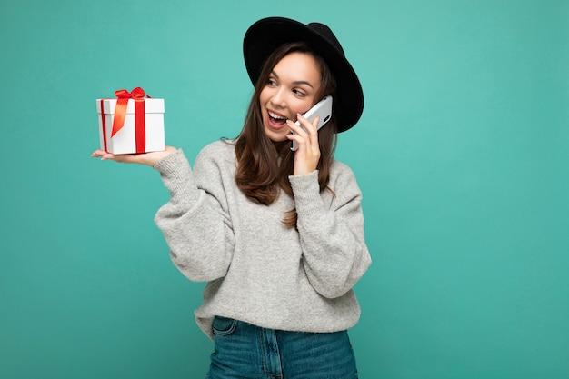 Vrolijke jonge brunette vrouw geïsoleerd op blauwe achtergrond muur dragen zwarte hoed en grijze trui houden geschenkdoos praten op mobiele telefoon en kijken naar de zijkant.