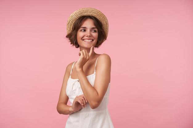 Vrolijke jonge brunette vrouw met casual kapsel wijsvinger op haar kin houden en vreugdevol over de schouder kijken, staande in boater hoed en elegante jurk