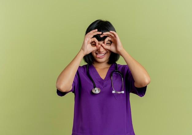 Vrolijke jonge brunette vrouwelijke arts in uniform met een stethoscoop kijkt door de vingers en steekt tong geïsoleerd op olijfgroene achtergrond met kopie ruimte