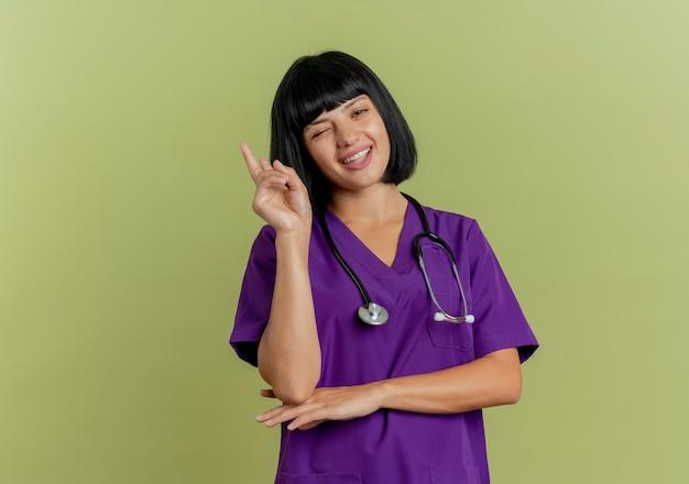 Vrolijke jonge brunette vrouwelijke arts in uniform met een stethoscoop knippert oog en wijst naar boven