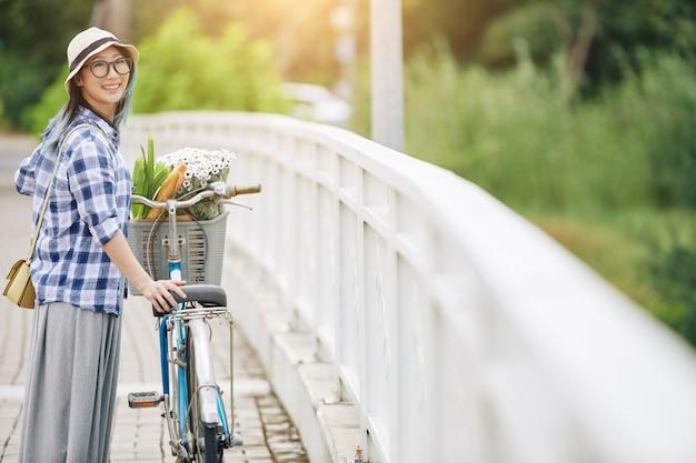 Vrolijke jonge chinese vrouw stading op brug naast fiets en terugkijkend op camera