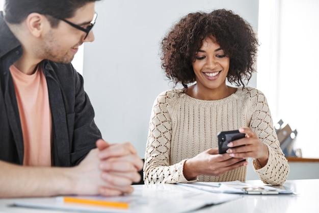 Vrolijke jonge collega's die samen smartphone gebruiken terwijl ze op kantoor aan tafel zitten