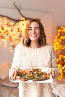 Vrolijke jonge dame die bij de verticale camera glimlacht houdt een doos met pizza.