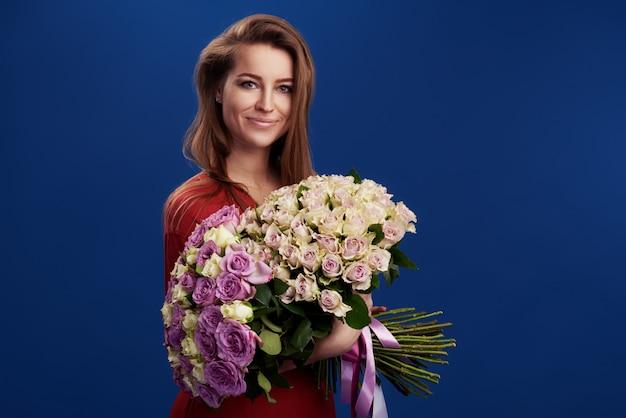 Vrolijke jonge dame die een groot boeket van kleurrijke tulpen op de dag of de verjaardag van vrouwen houdt die over blauw wordt geïsoleerd.