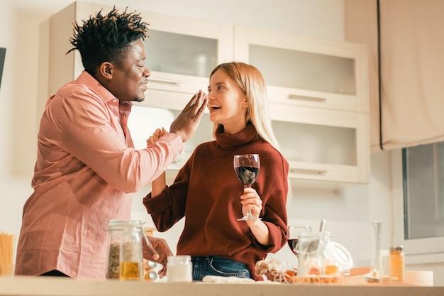Vrolijke jonge dame die in de keuken staat met een glas wijn en lacht terwijl haar vriendje wat bloem op haar neus zet