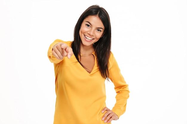 Vrolijke jonge dame die in geel overhemd aan u richt.