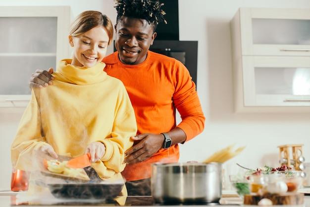 Vrolijke jonge dame die lacht en groenten op de koekenpan zet terwijl haar vriendje achter haar rug staat en haar schouder zachtjes knuffelt