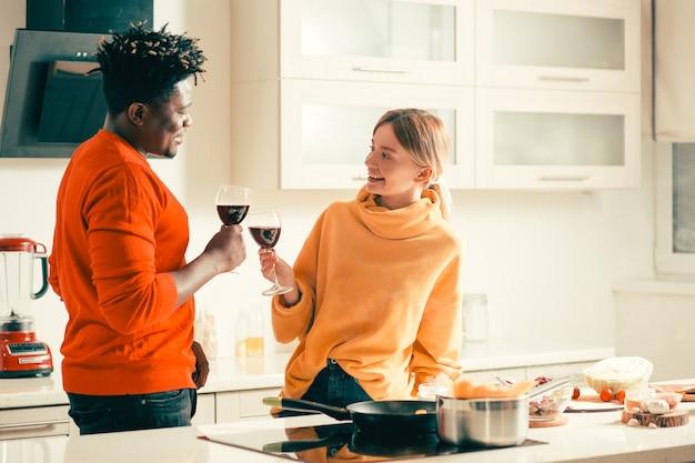 Vrolijke jonge dame die naast het fornuis en de koekenpan staat terwijl ze naar haar vriend glimlacht en wijn met hem drinkt