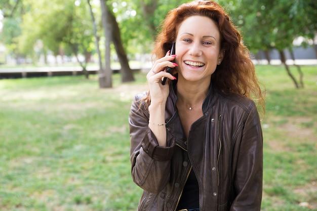 Vrolijke jonge dame die op telefoon in stadspark spreekt
