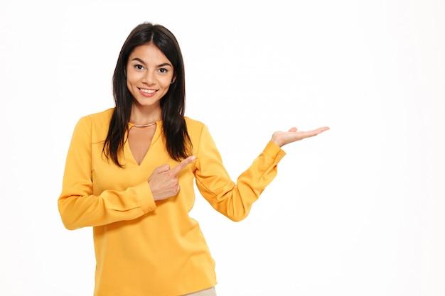 Vrolijke jonge dame in gele overhemd die copyspace ter beschikking houden.