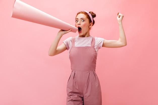 Vrolijke jonge dame in roze jurk en wit t-shirt schreeuwen in mondstuk op roze achtergrond.